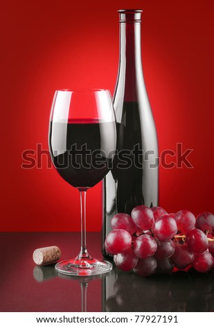 Red wine and ripe fruits of grapes on a glass surface - stock photo