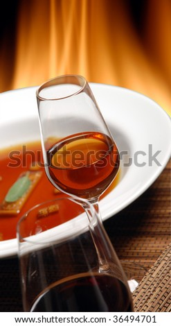 red wine and rose with a plate and fireplace in the background - stock photo