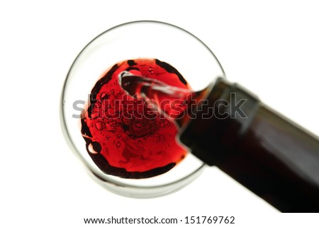 red wine being poured into a glass isolated on white-blurry movement - stock photo