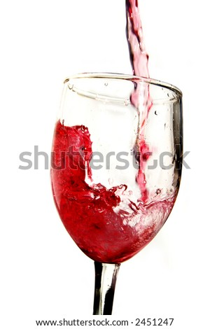 Red wine being poured into a glass, on white