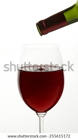 Red wine being poured into crystal glass on bright white background