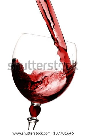 Red wine being poured into glass, white background