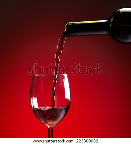 Red wine being poured into wine glass on red background