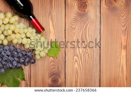 Red wine bottle and bunch of grapes on wooden table background with copy space - stock photo