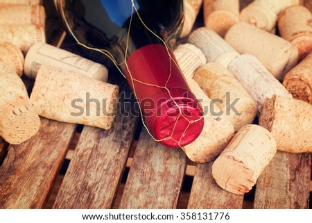 red wine bottle and corks on wooden table, retro toned - stock photo