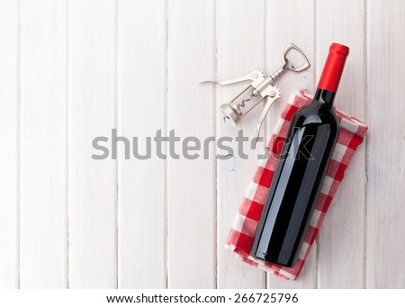 Red wine bottle and corkscrew on white wooden table background with copy space - stock photo