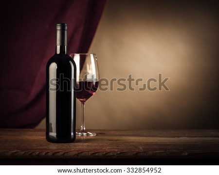 Red wine bottle and glass on a rustic wooden table, red cloth on background, wine tasting still life - stock photo
