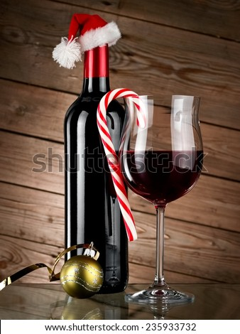 Red wine bottle and glass with Xmas lollipop and ball on  wooden background - stock photo