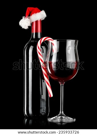Red wine bottle and glass with Xmas lollipop on black background - stock photo