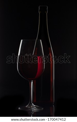 Red wine bottle and wine glass on black background