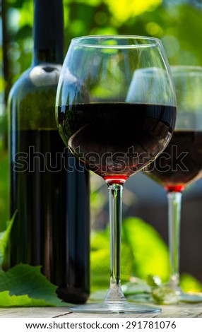Red wine bottle and wine glass on wooden table - stock photo