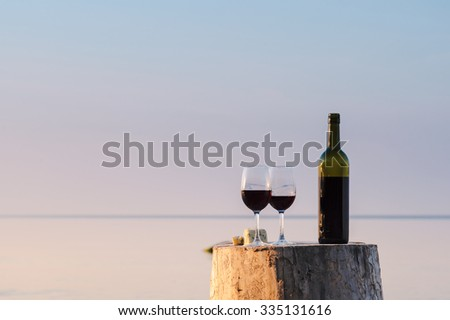 Red wine bottle and wine glasses on the shore in evening - stock photo