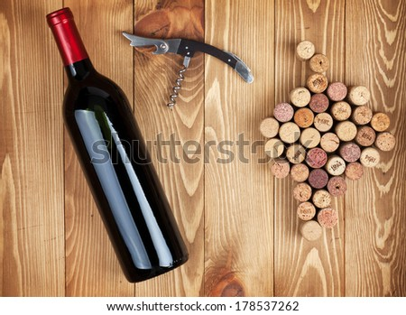 Red wine bottle, corkscrew and grape shaped corks on wooden table background - stock photo