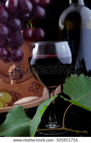 Red wine bottle, glass and cask with grapes over black - stock photo