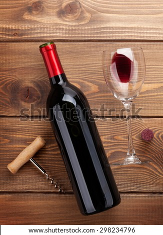 Red wine bottle, glass and corkscrew on wooden table background. Top view - stock photo