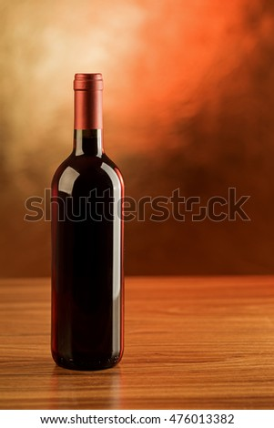 Red wine bottle on wooden table and red background