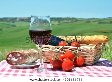 Red wine, bread and tomatos on the chequered cloth against Tuscan landscape. Italy - stock photo
