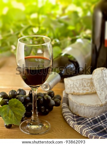 Red wine, Brie, Camembert and grape on the wood surface, outdoor - stock photo