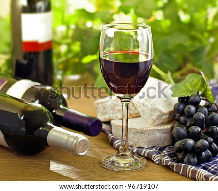 Red wine, Brie, Camembert and grape on the wood surface, outdoor