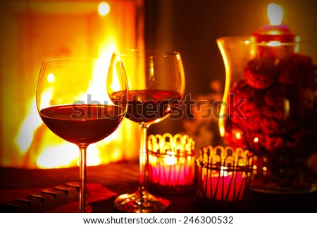 Red wine by the fireplace - stock photo