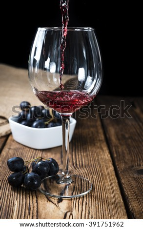 Red Wine (close-up shot) on vintage wooden background - stock photo