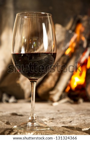 Red wine cup, glass. Fire background - stock photo