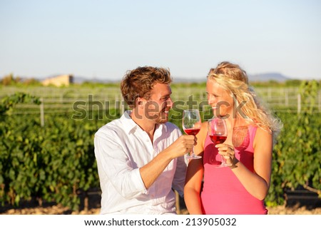 Red wine drinking couple toasting at vineyard. People drinking red or rose wine smiling happy doing toast. Romantic lovers outside. Young Caucasian man and woman. - stock photo
