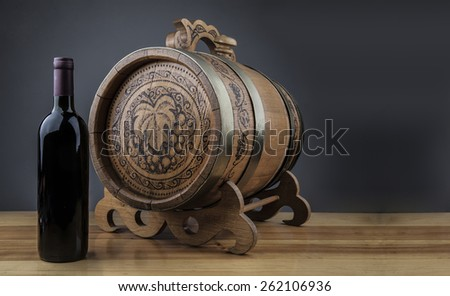 Red wine full dark glass bottle stand near wooden barrel on natural material table with reflection against black background Empty space for inscription Food and drink backdrop - stock photo