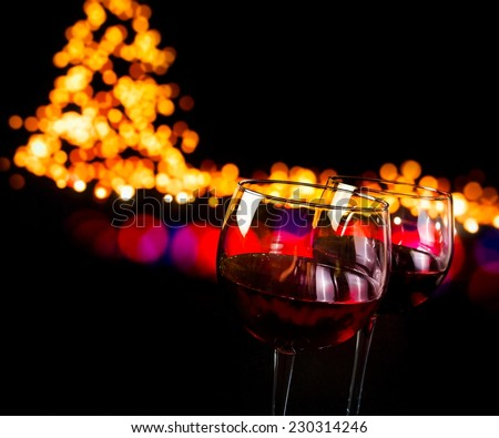 red wine glass against bokeh lights background, christmas atmosphere