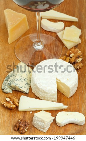 red wine glass and assortment of cheeses on wooden plate close up
