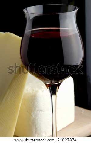 red wine glass and bottle and yellow and white cheese