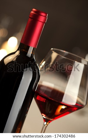 Red wine glass and bottle close up with restaurant on background.