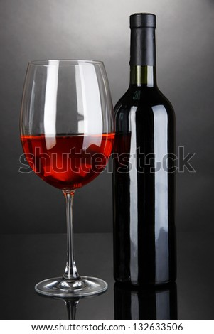 Red wine glass and bottle of wine on grey background