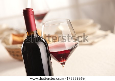 Red wine glass and bottle still life at restaurant.