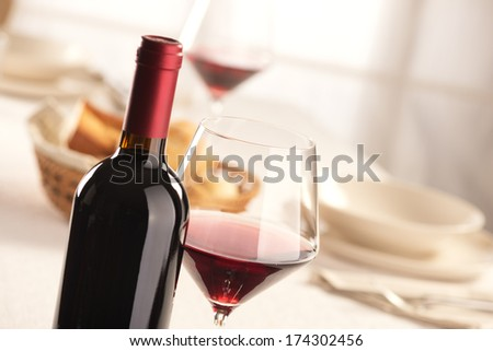 Red wine glass and bottle still life at restaurant. - stock photo