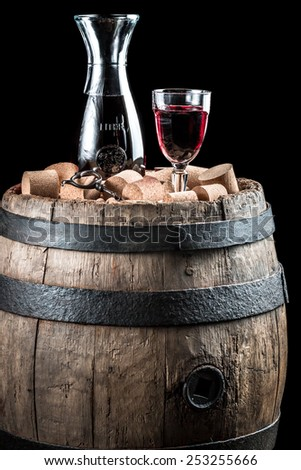 Red wine glass and carafe on old wooden barrel - stock photo