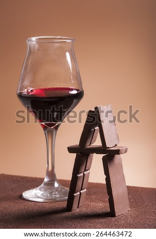 Red wine glass and chocolate pyramid - stock photo