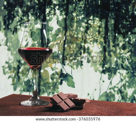 Red wine glass and chocolate with green leaves abstract background - stock photo