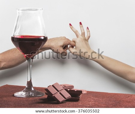 Red wine glass and chocolate with sex gesture - stock photo