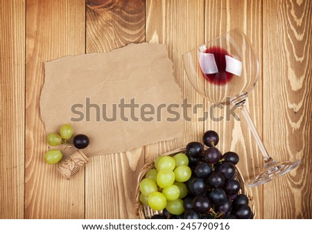Red wine glass and grape on wooden table background with copy space - stock photo