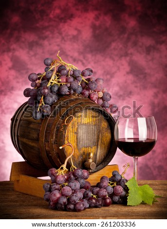 Red wine glass barrel with grapes on wooden table. - stock photo