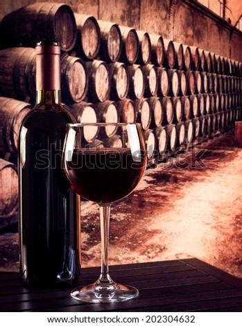 red wine glass near bottle in the old wine cellar with barrels background - stock photo