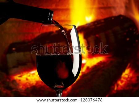 red wine glass near fireplace - stock photo