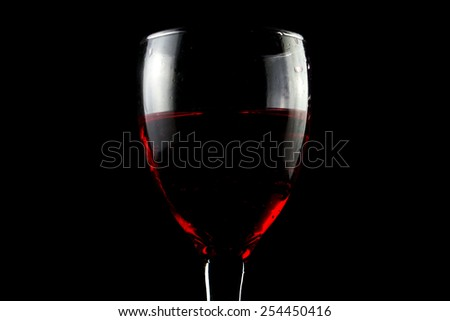 Red wine glass on black background - stock photo