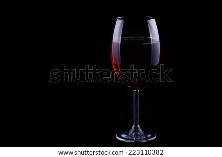 Red wine glass on the black background, shallow focus - stock photo