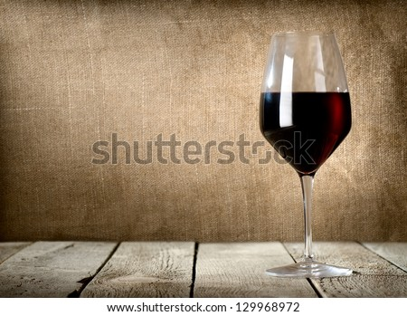 Red wine glass on the wooden table - stock photo