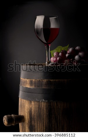 red wine glass on wooden barrel isolated on black gradient