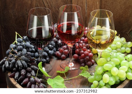 Red wine glass, rose wine glass, white wine glass, red wine grapes, white wine grapes, wine barrel - stock photo