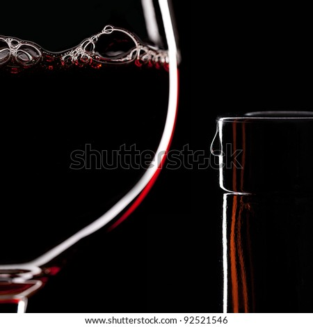 Red Wine Glass silhouette on Black Background with Bubbles and bottleneck with a drop - stock photo