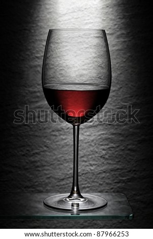 Red wine glass spot lighted in front of stone granite wall - stock photo